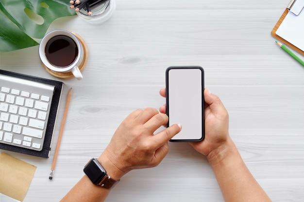 コンピューター、事務用品、コーヒーカップをオフィスの白い木製机テーブルに携帯電話を使用している人。