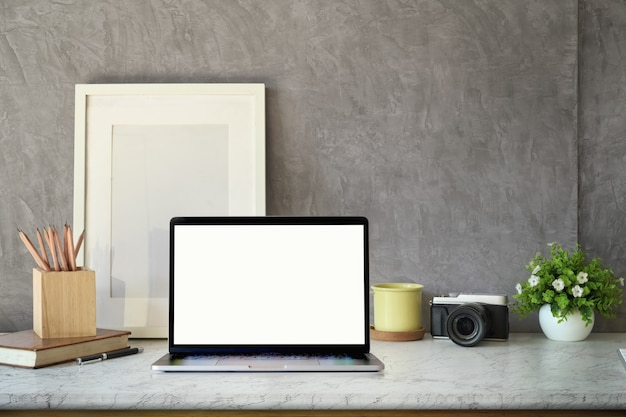 クリエイティブワークスペース、空白の画面のノートパソコン、モックアップポスター、机の上のビンテージカメラ