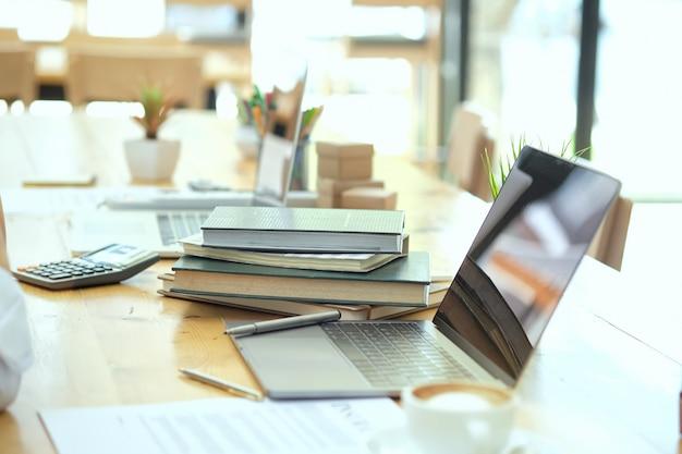 ノートパソコンと朝の光で木のテーブル上の本の職場。