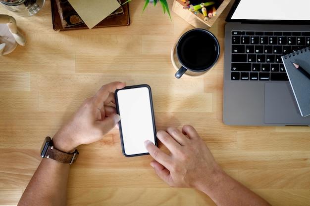 スマートフォンとオフィスでラップトップを使用して認識できないビジネスマンのクローズアップショット