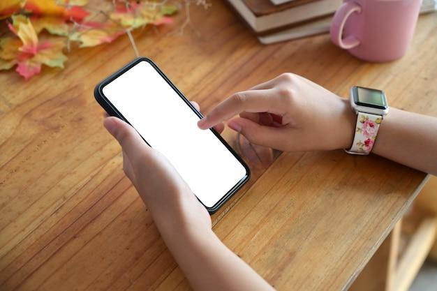 空白の画面を持つ携帯電話を保持している女性の手のクローズアップ。