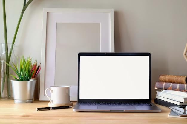 ノートパソコンと机の上のポスターと現代的なワークスペースデスク。