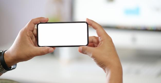 ビジネスマンのオフィスの机の上に白い画面で携帯電話をかざす