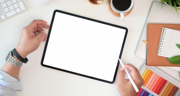 Рука графического дизайнера работая с карандашем стилуса и рисуя таблеткой в офисе