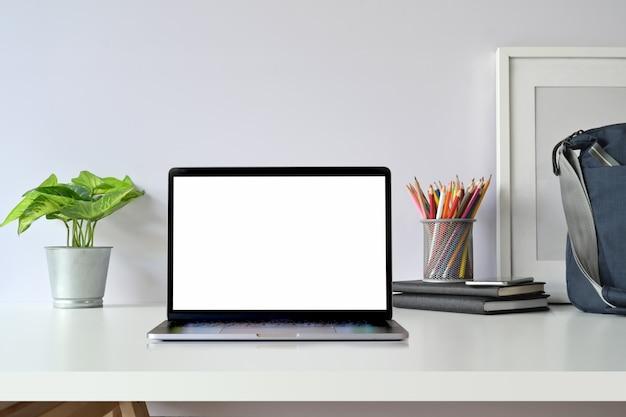 Креативное рабочее пространство, пустой экран ноутбука, макет постера и винтажная камера на столе