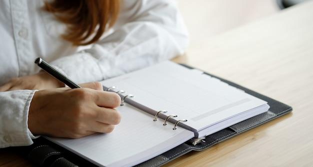 女性の手が机の上の空白のノートブックに書く