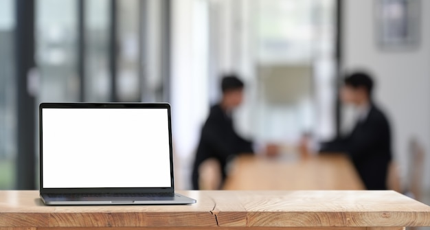 オフィスの木製の机の上の空白の画面を持つノートパソコン