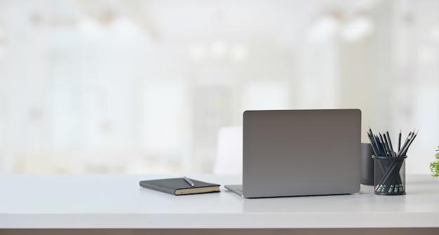 オフィスのワークスペースのテーブルの上のラップトップコンピューター。