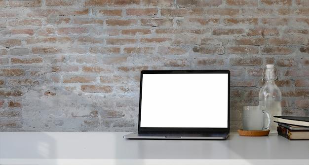 ワークスペースの机の上の空白の白い画面を持つノートパソコンを開く