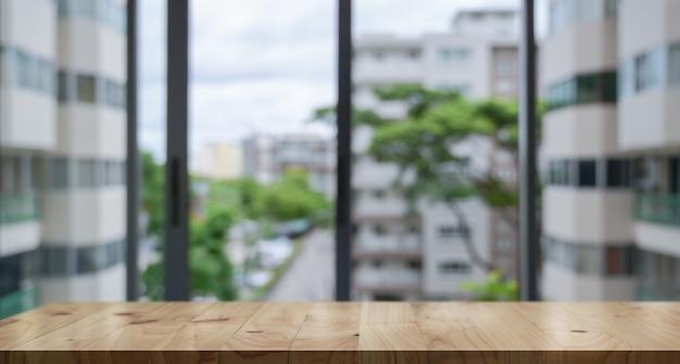 空の木製テーブルトップとぼかしガラス窓壁建物バナーの背景