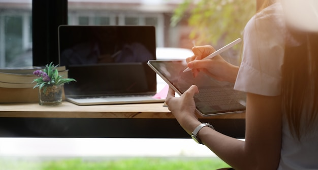 Молодая женщина в библиотеке с помощью планшета
