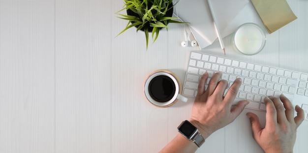 最小限の白い作業スペースでキーボードで入力する人