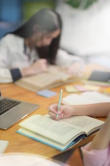 ノートを取っている若い女の子の手のクローズアップ