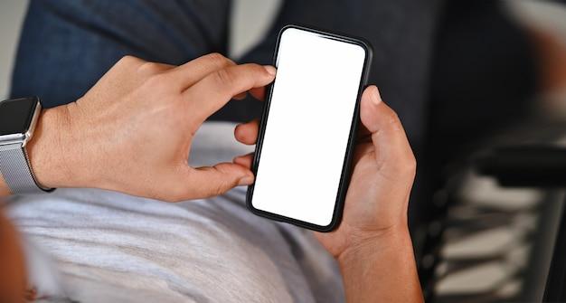空白の画面のスマートフォンを持っている男の手