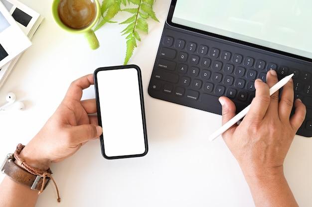 白い背景の上の空白の画面モバイルスマートフォンを持ってトップビュー男