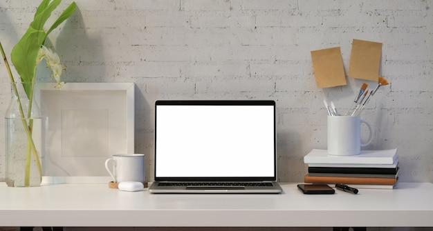 事務用品と開いた空白の画面のラップトップ