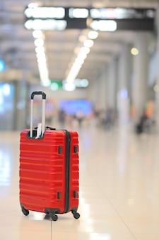 Красный чемодан или багаж в терминале аэропорта.