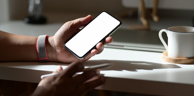 Молодой мужчина фрилансер ищет идеи со смартфона