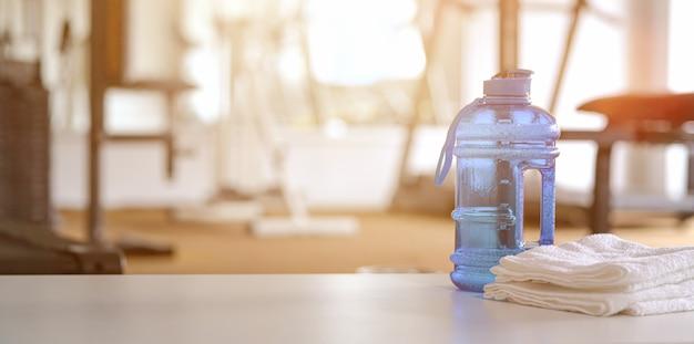 Полотенца и спортивные бутылки с копией пространства в тренажерном зале