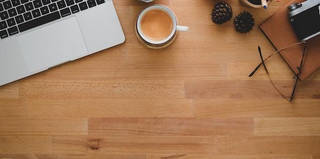 Вид сверху удобного рабочего места с ноутбуком, чашкой кофе и канцелярскими товарами