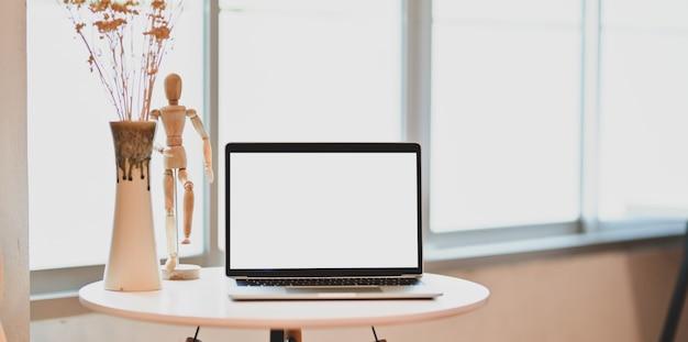 開いた空白画面のラップトップと白いテーブルの装飾と現代的な職場
