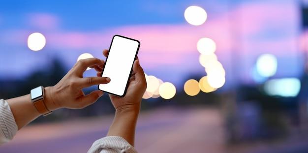 空白の画面のスマートフォンに触れる男のクローズアップビュー