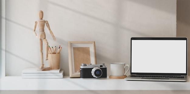Фотограф творческая студия с пустым экраном ноутбука и офисными аксессуарами
