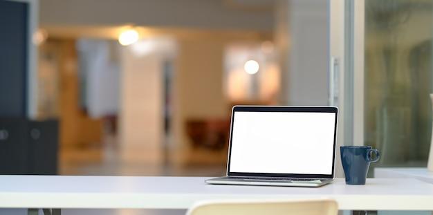 空白の画面のラップトップコンピューターとコーヒーカップを開く
