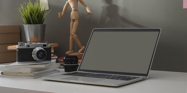 Минимальное рабочее место фотографа с открытым ноутбуком и винтажной камерой