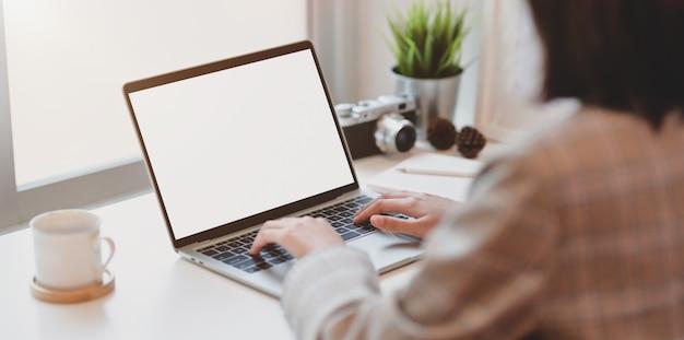 空白の画面のラップトップコンピューターに入力する若い実業家