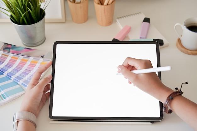スタジオでデジタルタブレットペンを使用してグラフィックデザイナーの手