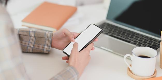 彼女の空白の画面のスマートフォンを保持している若い実業家