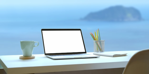 海ビューの背景を持つオープンラップトップと現代の職場