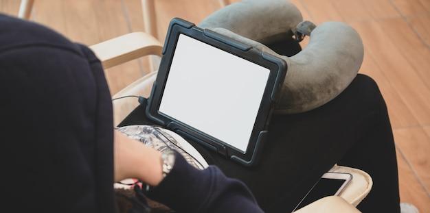 空白の画面のタブレットを見ながら椅子でリラックスできる女性