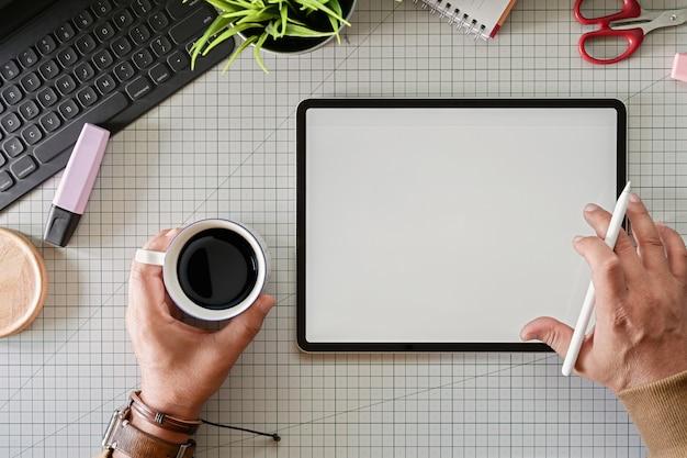 スタジオで革新的なタッチスクリーン現代タブレットを使用したクリエイティブグラフィックデザイナー