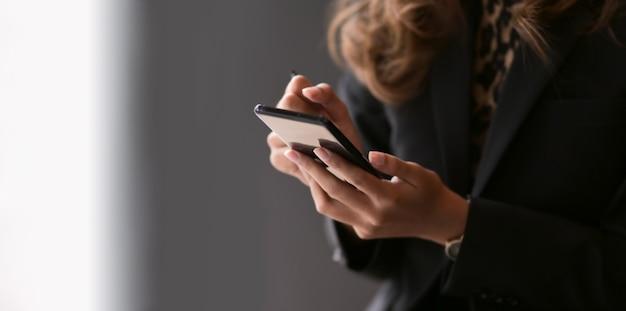 空白の画面のスマートフォンを保持している実業家のクローズアップビュー