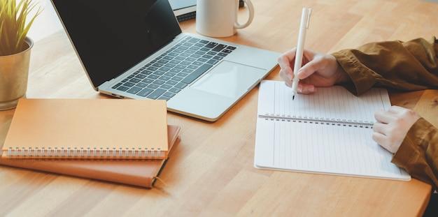 Взгляд конца-вверх женщины писать ее идею на тетради