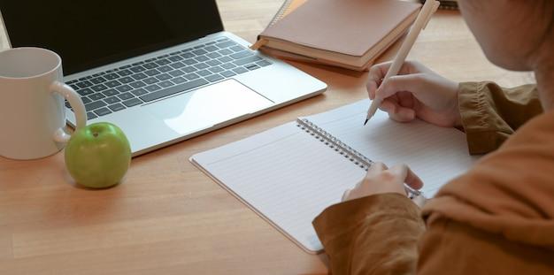Женщина пишет свою идею на ноутбуке во время работы над проектом в уютной комнате