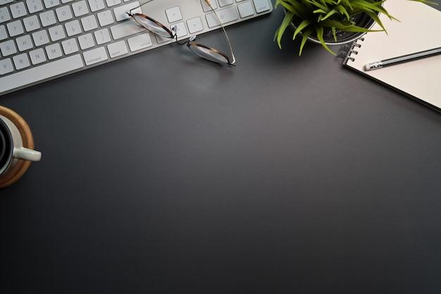 Вид сверху черного офисного стола с клавиатурой компьютера, канцелярских принадлежностей и копией пространства