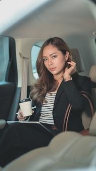 Профессиональная азиатская коммерсантка смотря пока сидящ на заднем сиденье автомобиля