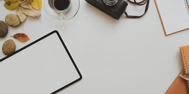 空白の画面のタブレット、ビンテージカメラ、コーヒーカップ、事務用品のコピースペースを持つ白いテーブル