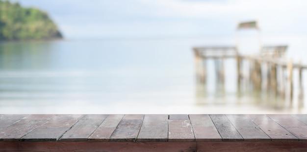 バックグラウンドで美しい熱帯のビーチと空の素朴な板