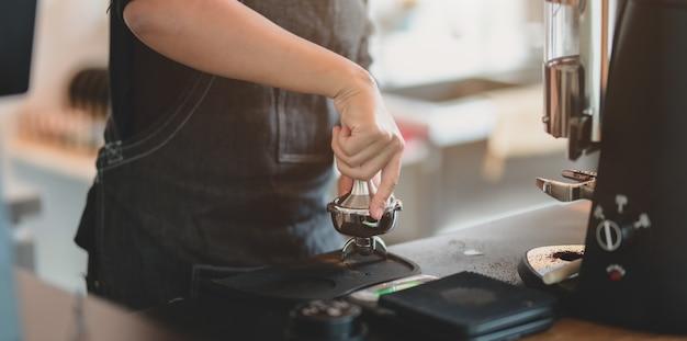 グラインダーマシンで女性のバリスタ手の研削コーヒーのクローズアップビュー
