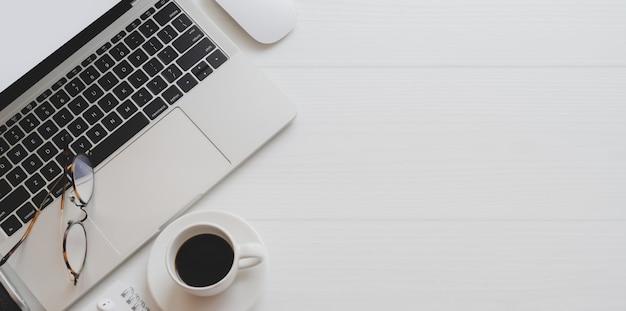 ラップトップコンピューター、コーヒーカップ、事務用品と最小限の職場のオーバーヘッドショット