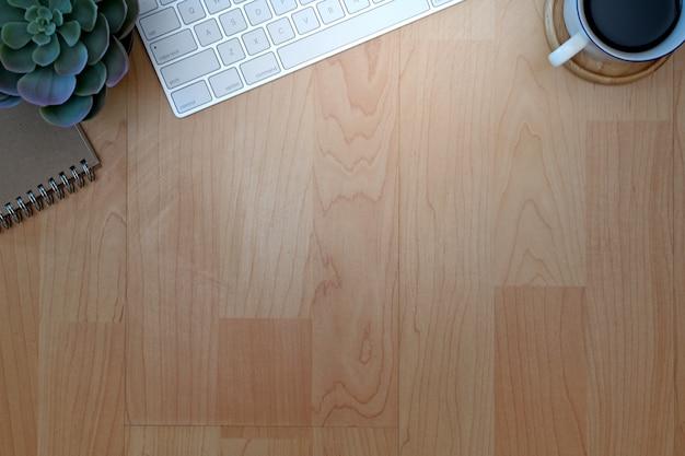 木製のテーブルの上のコーヒー・マグ、キーボード、事務用品のある職場の平面図