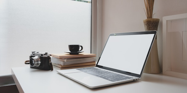 開いている空白画面のラップトップ、ビンテージカメラ、コーヒーカップと最小限の写真家職場