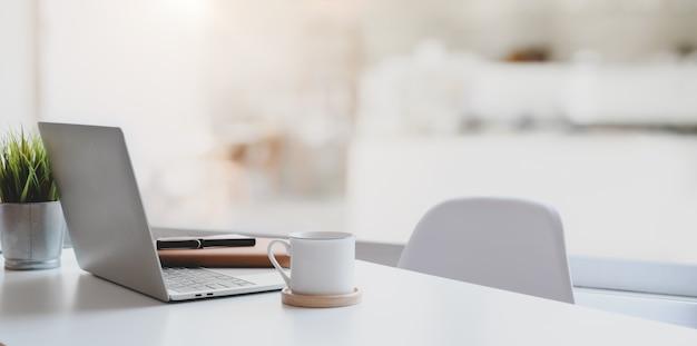 Современное рабочее место с ноутбуком, кофейной чашкой и канцелярскими товарами