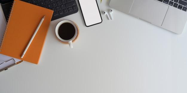 事務用品と白い木製の机の上の空白の画面のスマートフォンで快適なワークスペースの平面図