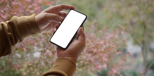 空白の画面のスマートフォンを保持している若い男のクローズアップビュー