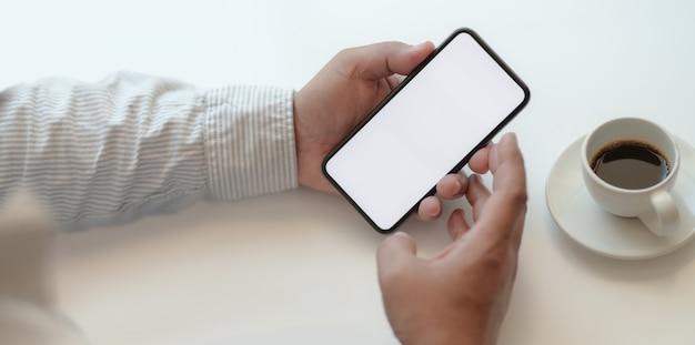 Бизнесмен, держа смартфон пустой экран в удобном рабочем пространстве
